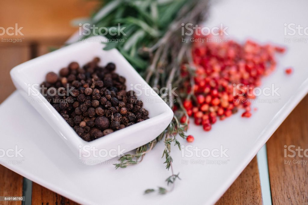 Rosemary with black and pink pepper corns on a white plate on wood background stock photo