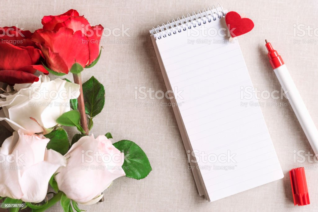 Roses and a blank spiral notebook with heart stock photo