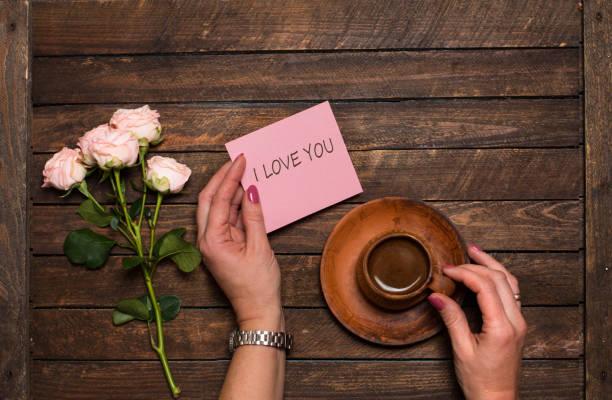Rosen und Kaffee. Tasse Kaffee und ein Strauß Rosen auf einem Holztisch. Morgenkaffee und Beachten Sie, ich liebe Sie in Frauen Hände. – Foto
