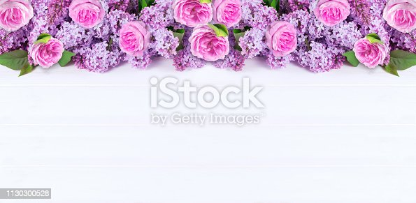 Pink roses and lilac flowers on white wooden boards