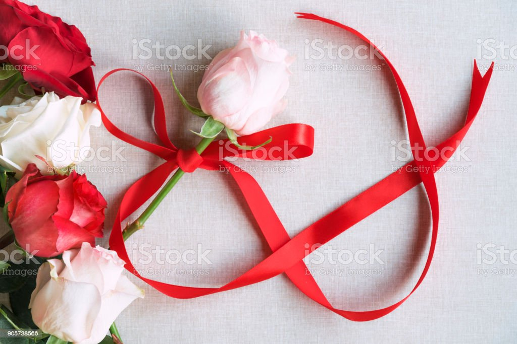 Roses and red ribbon in shape of infinity stock photo