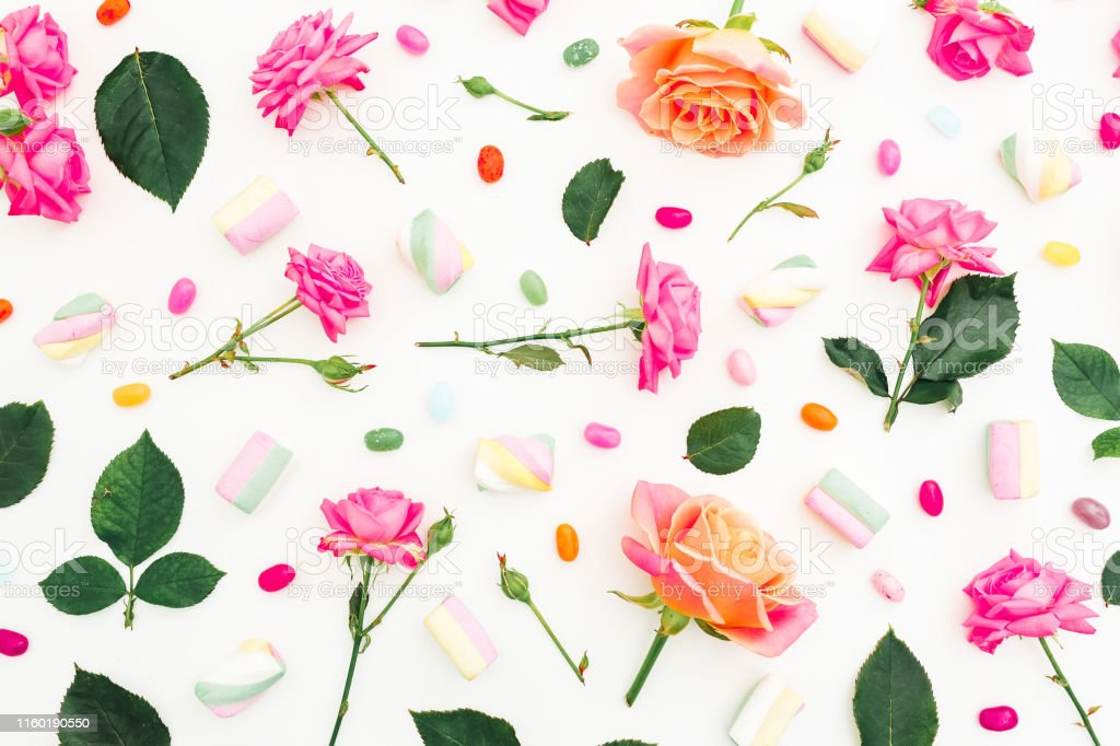 Roses flowers with bright sugar candy on white background. Flat lay,...