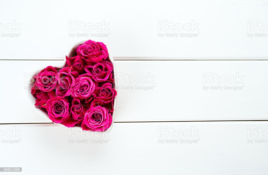 roses in a heart-shaped bowl stock photo