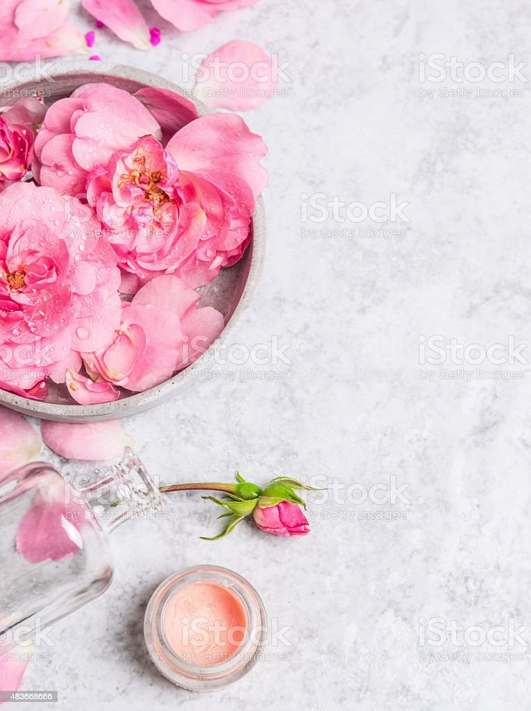 Roses in bowl with water , cream  on  stone background stock photo