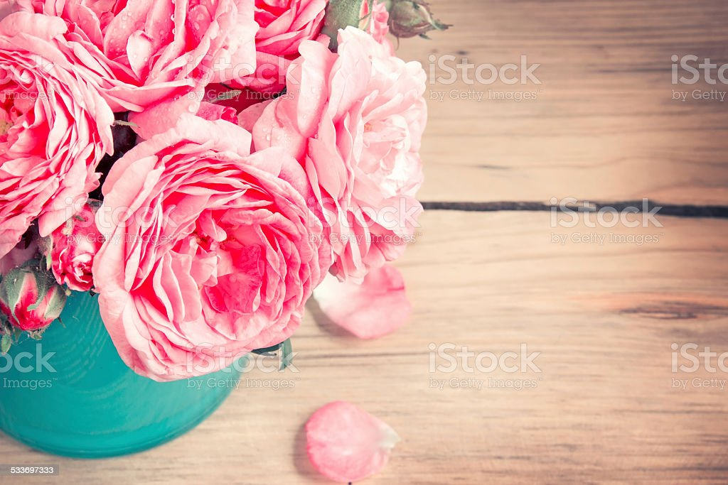 Roses in vase on wooden background. stock photo