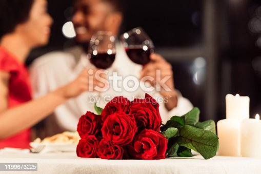 Valentine's Romantic Date. Red Roses Lying On Table, Unrecognizable Spouses Drinking Wine In Restaurant. Selective Focus, Cropped