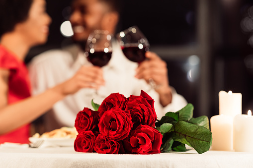 Roses Lying On Table, Unrecognizable Spouses Drinking Wine In Restaurant