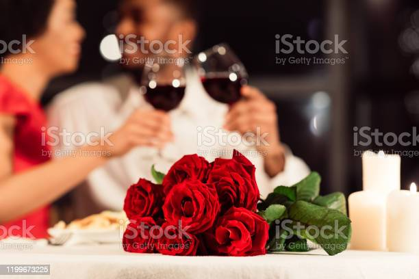 Photo of Roses Lying On Table, Unrecognizable Spouses Drinking Wine In Restaurant