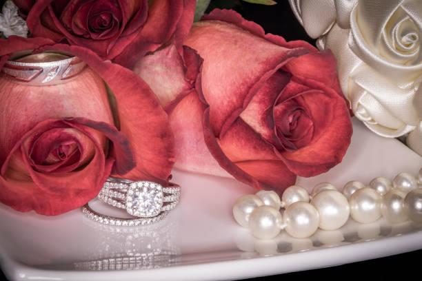 rosen auf weißen teller mit trauringe, perlen & bouquet - tischdeko goldene hochzeit stock-fotos und bilder