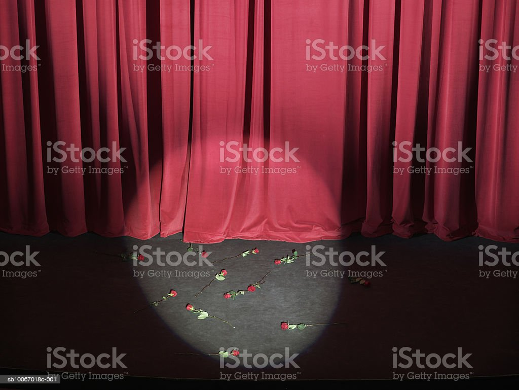Roses strewn on empty stage with curtains closed and spotlight on royalty-free stock photo