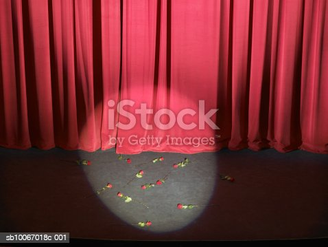 istock Roses strewn on empty stage with curtains closed and spotlight on sb10067018c-001
