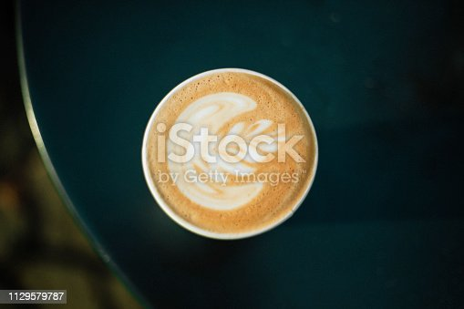 A directly above shot of a artistic rossetta leaf on a hot cup of coffee in a cafe in New York City.