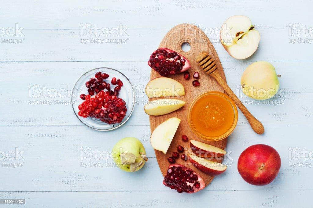 Rosh Hashana. Jewish New Year Holiday. Traditional table set with honey, apple and pomegranate. Flat lay. stock photo