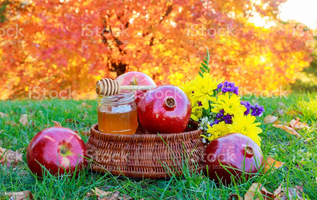 rosh hashanah concept - apple honey and pomegranate over wooden table stock photo