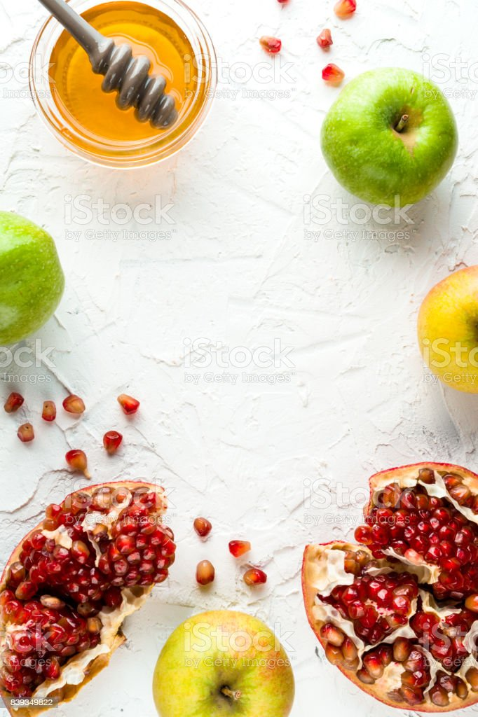 Rosh Hashanah frame of grains of pomegranate, honey and apples on a white background stock photo