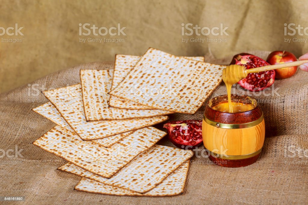 Rosh hashanah jewesh New Year holiday concept - pomegranate, honey and apple over glitter background. stock photo
