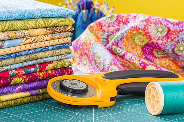 rotary cutter and spool of thread - quilt stock photos and pictures