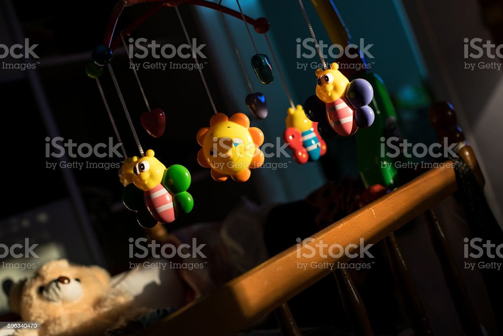 Rotating baby toys attached on a bed, without baby royalty-free stock photo