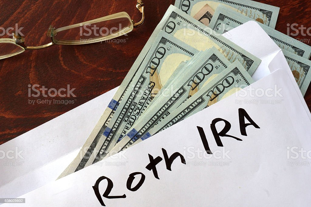 Roth IRA written on an envelope with dollars. stock photo