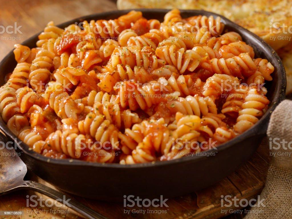 Rotini Nudeln mit gebratenen Tomaten und Knoblauch-Sauce mit Knoblauchbrot – Foto