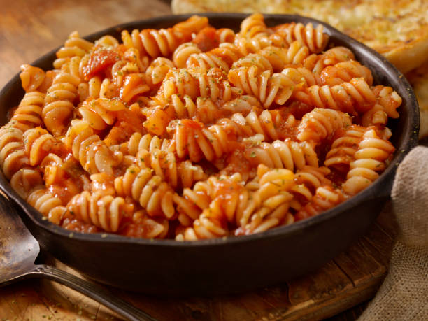 Rotini Pasta in Roasted Tomato and Garlic Sauce with Garlic Bread Rotini Pasta in Roasted Tomato and Garlic Sauce with Garlic Bread fusilli stock pictures, royalty-free photos & images