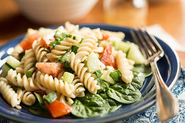Rotini Pasta Salad with Spinach Pasta salad with spinach, cucumber, tomato and spring onion. fusilli stock pictures, royalty-free photos & images