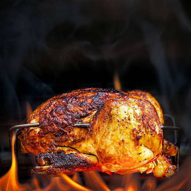 Rotisserie Chicken Cooking Over Open Flames Charred rotisserie chicken over open flames in a barbecue. Square format with room for text spit roasted stock pictures, royalty-free photos & images