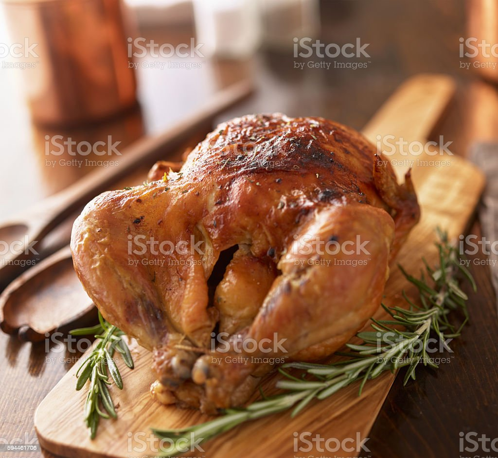 rotisserie chicken on wooden serving tray stock photo