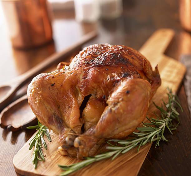rotisserie chicken on wooden serving tray - girarrosto foto e immagini stock