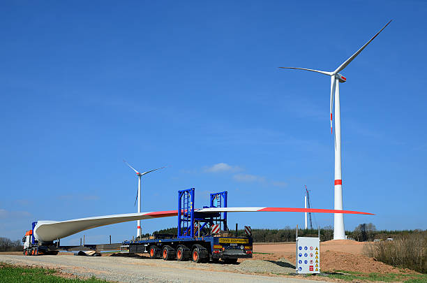 Rotor blade on low loader truck with wind turbines stock photo