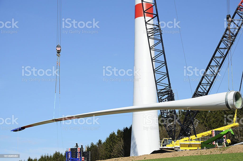 Rotor blade on wind turbine construction site with cranes royalty-free stock photo