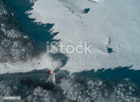 Rotor Snow-plough working over a winter mountain road, view from above, drone shot