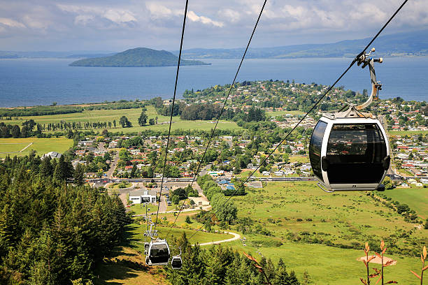 rotorua,new zealand Image of cable car with lake and mountains of  Rotorua, New Zealand in the background rotorua stock pictures, royalty-free photos & images