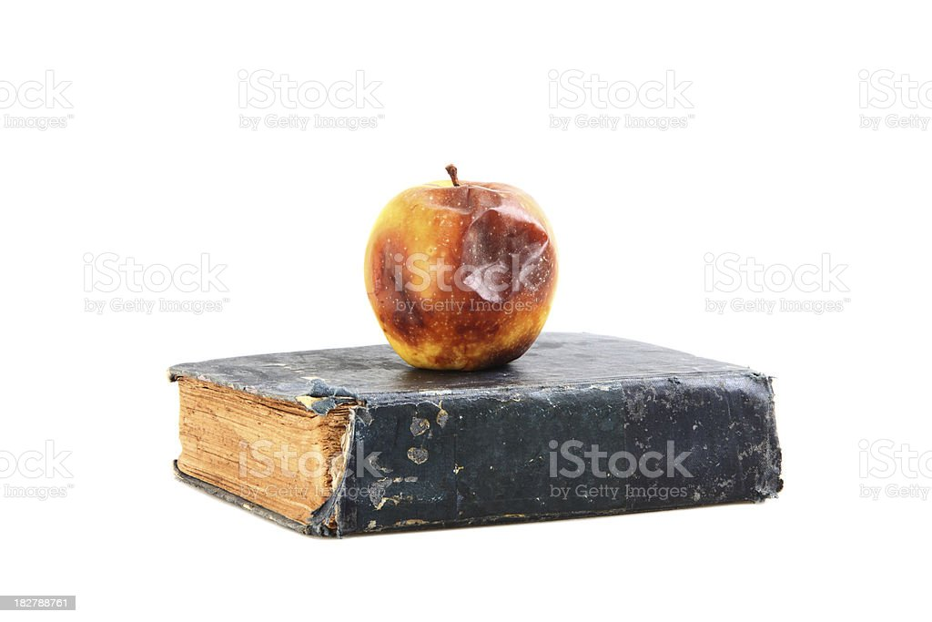 Rotten Apple on Top of Old Book, Outdated Education System stock photo
