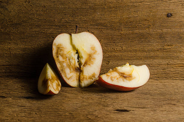 Rotten apple Rotten apple on wooden board background addle stock pictures, royalty-free photos & images