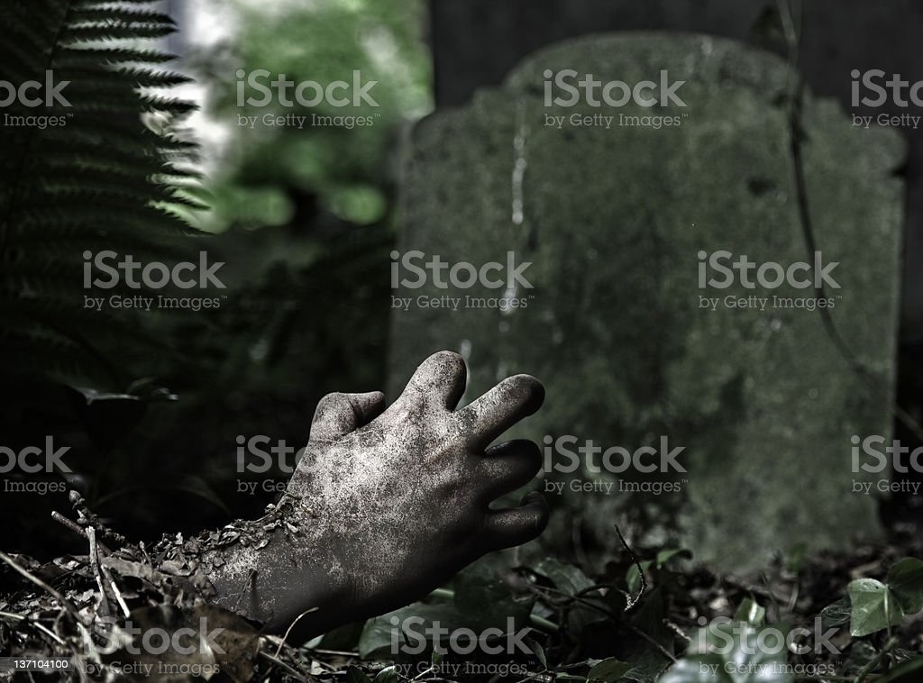 A rotting hand reach out from under the grave stock photo