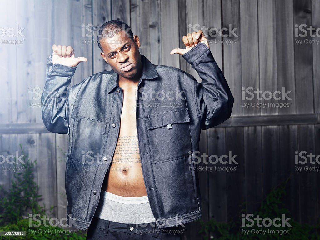 rough african guy posing in front of fence stock photo