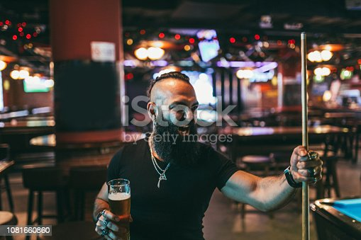 Rough man with long beard playing snooker in a pub and drinking beer