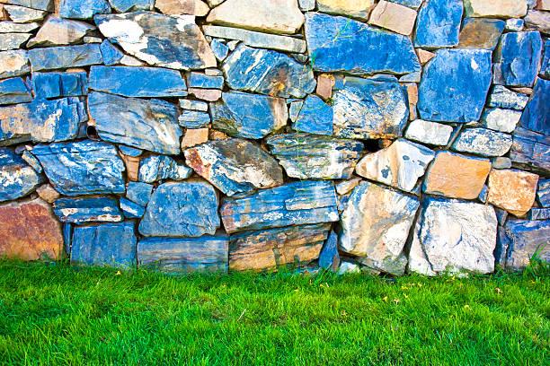raue und trockene stein mauer und grünem gras - steine für gartenmauer stock-fotos und bilder
