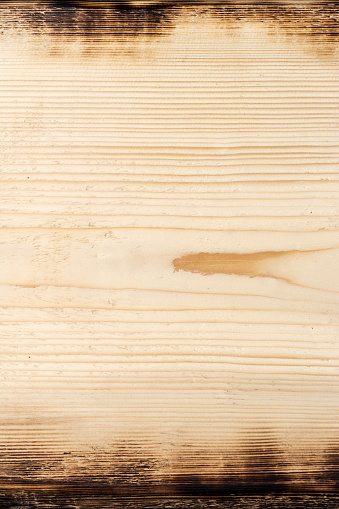 Rough, light grunge wood texture. Damages and scratches are clearly visible. Edges of the board are burnt.