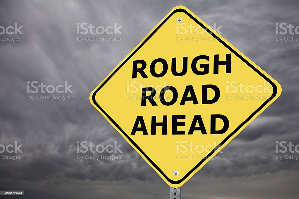 Rough Road Ahead Sign on Stormy Sky royalty-free stock photo