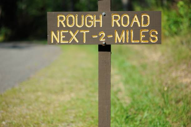 Rough road next two miles sign stock photo