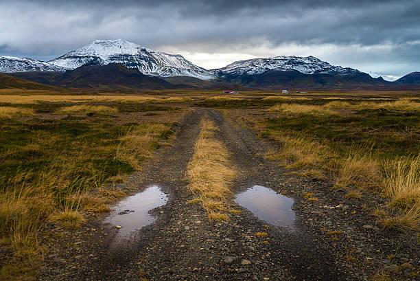Áspero carretera perspectiva en campo amarillo con el fondo de montaña con nieve - foto de stock