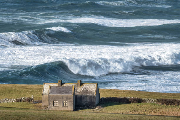 Rough Sea and a Lonely Cottage Rough sea with large waves on the Irish coastline in County Clare near the Cliffs of Moher county clare stock pictures, royalty-free photos & images