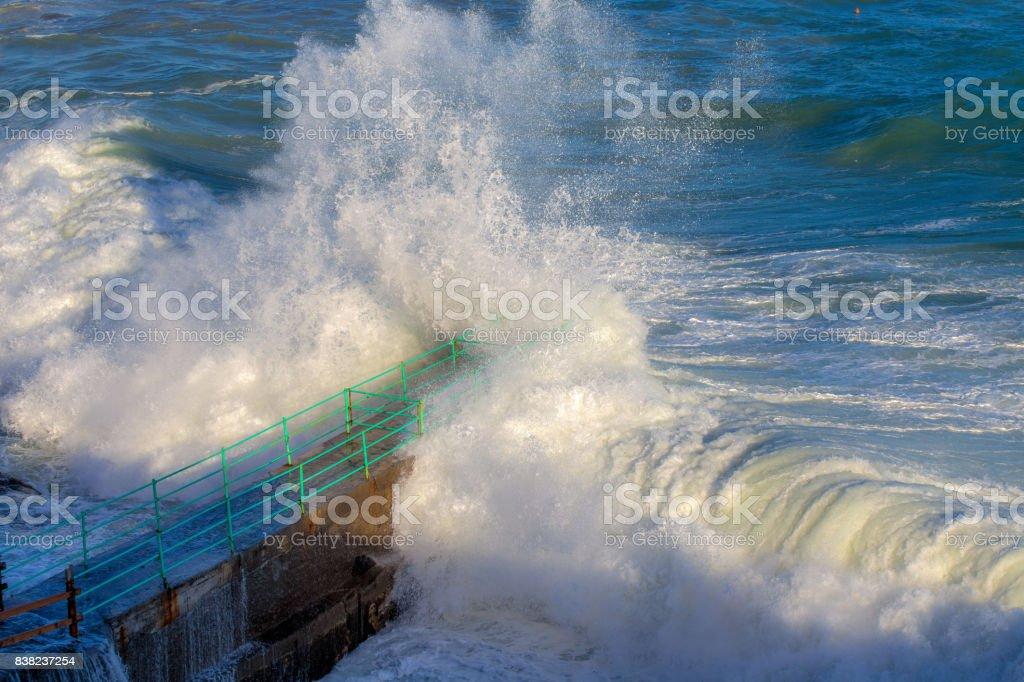 Rough Sea Waves Crashing Over a Pier, mediterranean sea, ligurian coast, Italy. stock photo