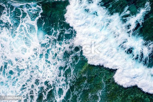 Sea waves seen from above, while splashing and flowing on a rocky seabed. Blue and cold hues. Aerial view.