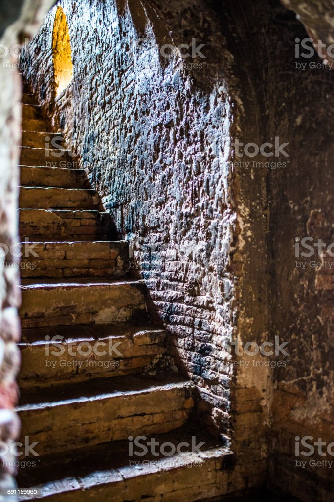 Rough stone wall and stairs in an ancient temple with illuminated light at the top stock photo