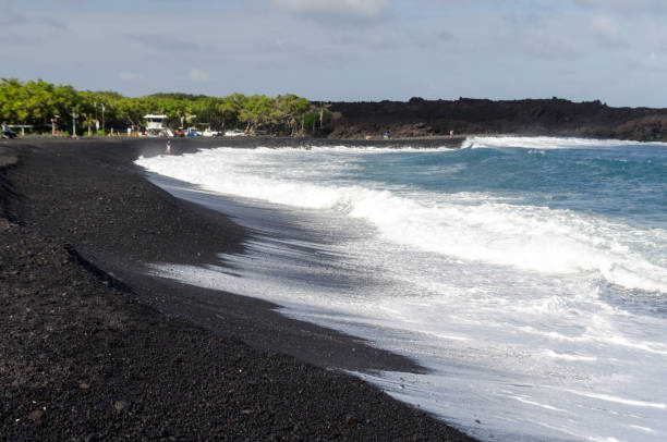 Rough surf  at edge of black sands of Pohoiki  beach, Isaac Hale Beach Park, Big Island, hawaii stock photo