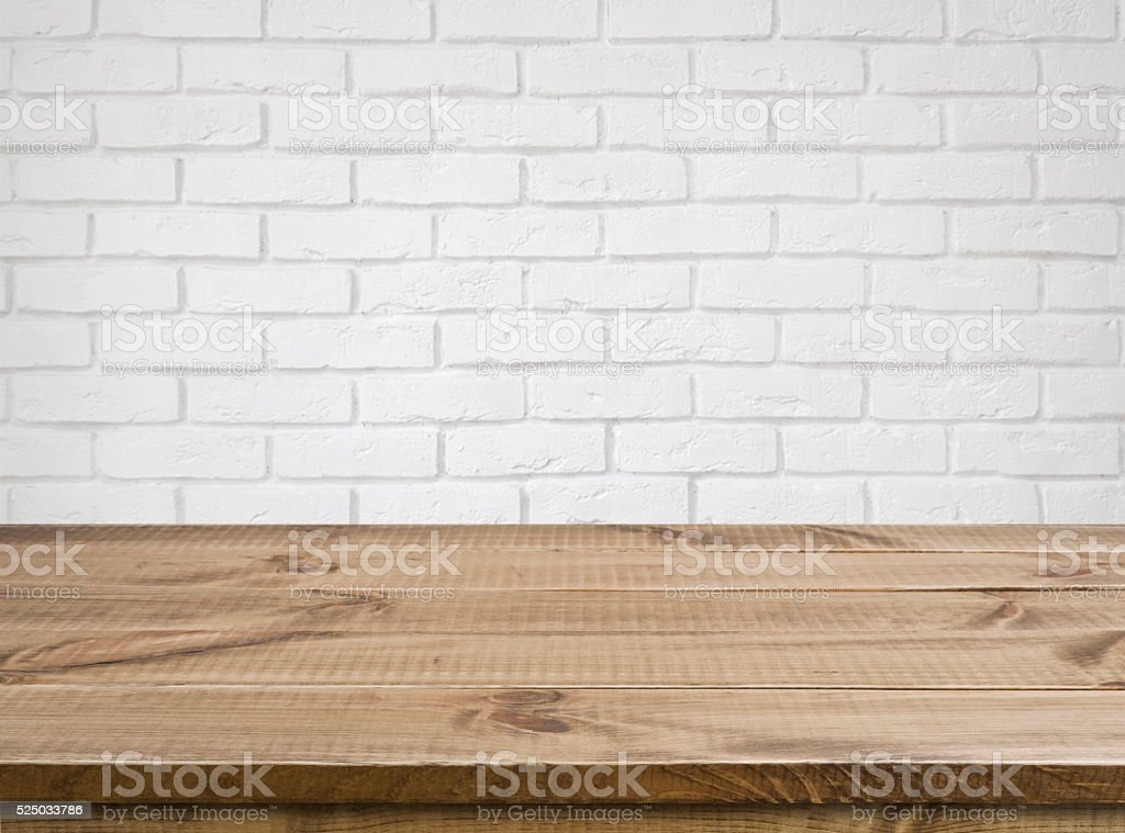 Rough wooden texture table over defocused white brick wall background stock photo