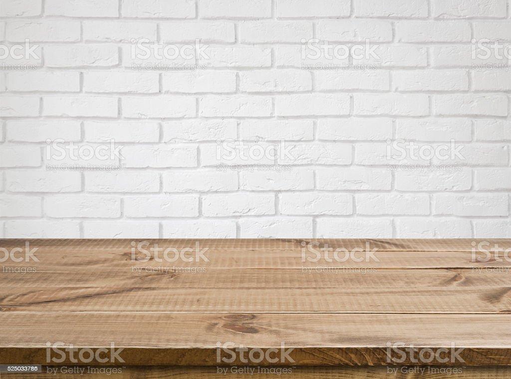 Rough wooden texture table over defocused white brick wall background bildbanksfoto